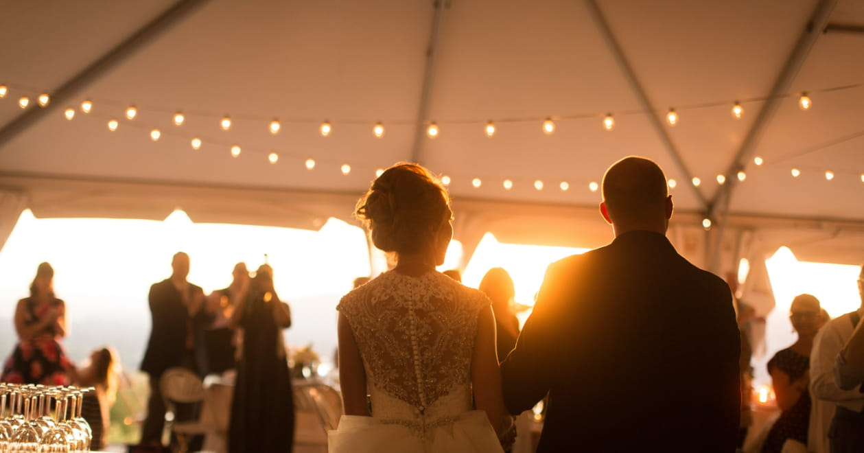wedding couple holding hands on the dance floor with sun setting